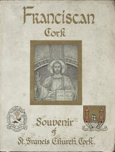 The front cover of 'Franciscan Cork: A Souvenir of St. Francis Church Cork.' The cover has detail from the apse of Christ in majesty. On the lower left is the Franciscan coat of arms and on the lower right is the coat of arms for Cork.