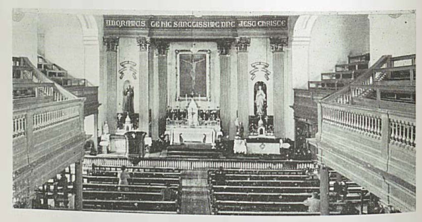 An image of the old St Francis Church in Cork City with pews in front of the altar. There are statues on either side of the altar and Latin writing over the altar and statues.