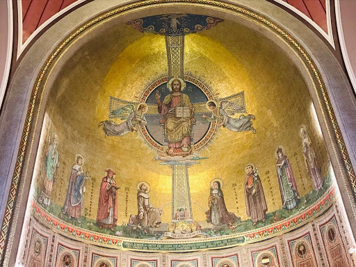Photo showing the apse in St Francis Church, Cork. The photo depicts Christ in Majesty seated holding a book in one hand and his other hand raised. Two angels are on either side and eight saints stand below him.
