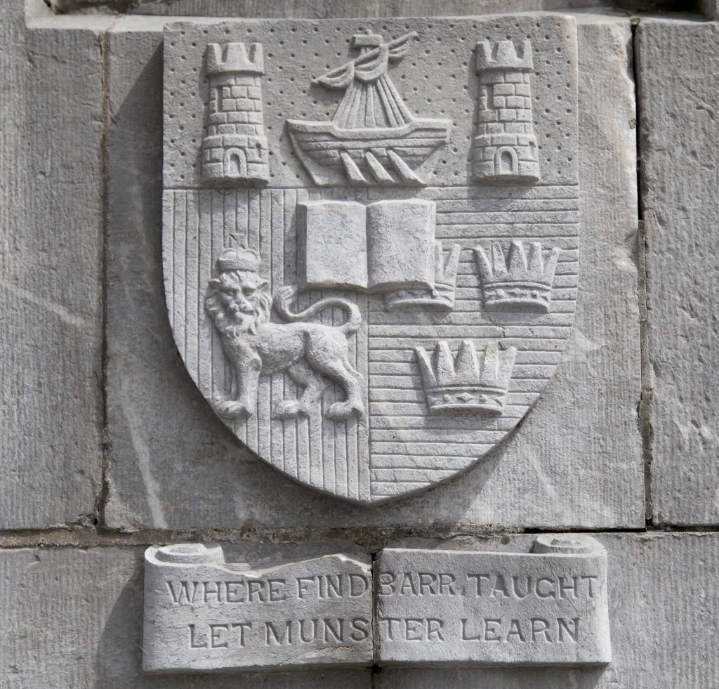 UCC Crest of a ship between two towers, a book in the centre which is flanked by a lion and two crowns. This is all on a shield. The shield is over the words 'Where Finnbarr Taught Let Munster Learn'. All are carved in grey stone.
