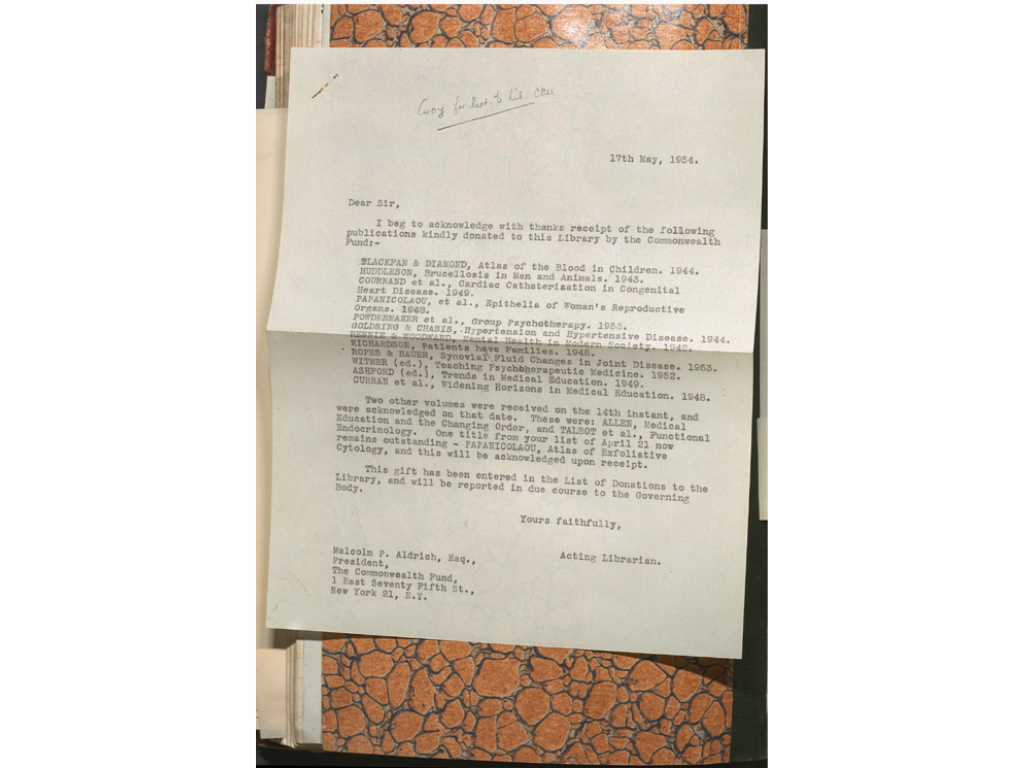 The rear verso endpaper with letter insert from the Donations Book 1931-1955. The letter is typed on white paper and placed on an orange & black marbled page.